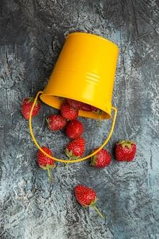 Morangos frescos dentro de uma cesta na mesa escura com vitamina de frutas vermelhas