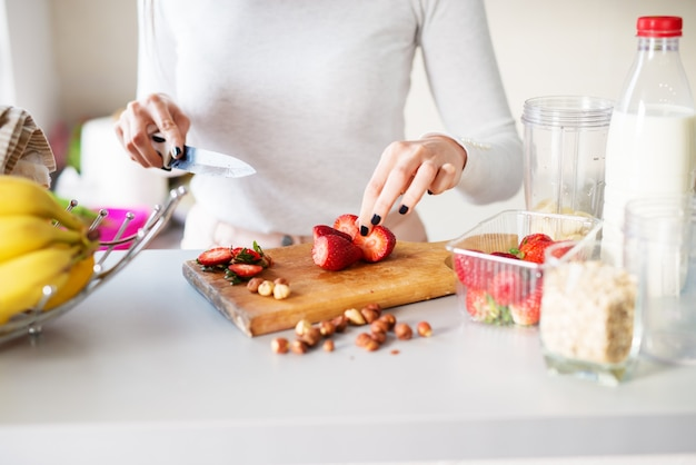 Morangos frescos direto do jardim estão sendo cortados por uma mulher em uma mesa brilhante da cozinha.
