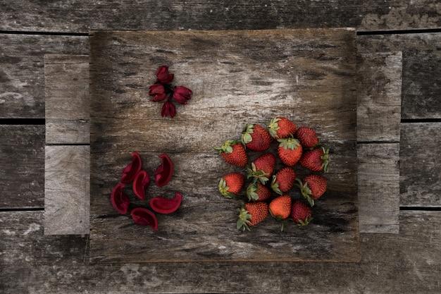 Morangos frescos e pétalas de flores vermelhas em uma superfície de madeira