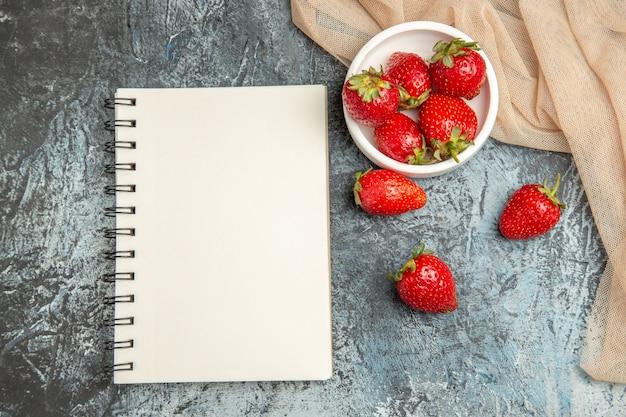 Morangos frescos e vermelhos de vista de cima com bloco de notas na superfície clara escura com frutas vermelhas