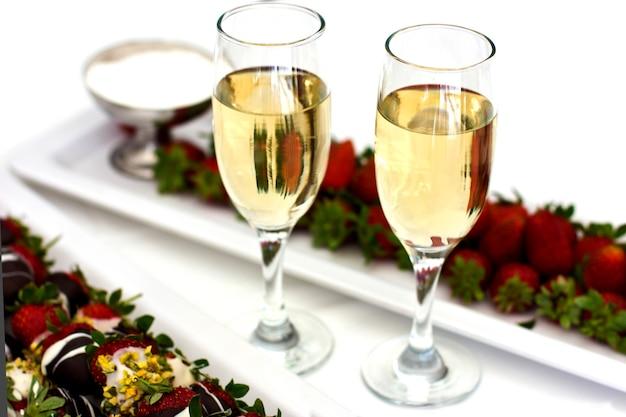 Morangos frescos em chocolate com chantilly e champanhe em copos
