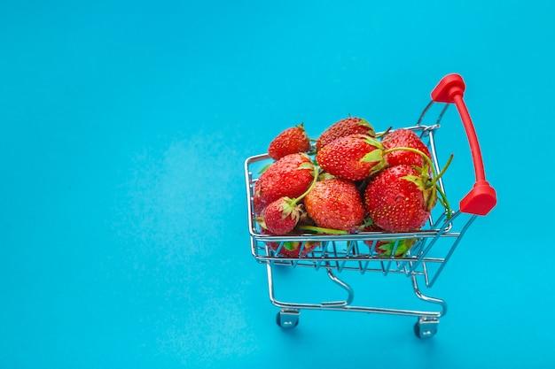 Morangos frescos em um carrinho de supermercado em um fundo azul.