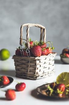 Morangos frescos em uma cesta na mesa de madeira branca