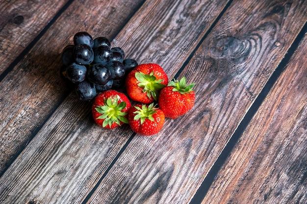 Morangos frescos escoceses e uvas pretas em cima da mesa de madeira.