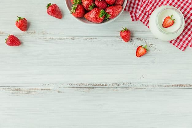 Morangos frescos na vista superior da tigela de cerâmica. comida saudável em maquete de borda de mesa de madeira branca
