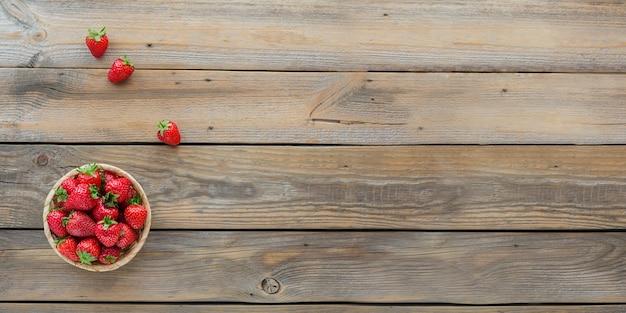 Morangos frescos na vista superior do cesto. comida saudável no banner de mesa de madeira simulado