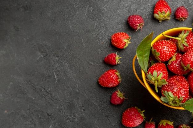 Morangos frescos vermelhos alinhados em mesa com frutas vermelhas frescas