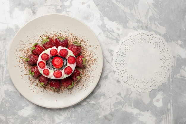 Morangos frescos vermelhos com bolo na mesa branca, vista de cima