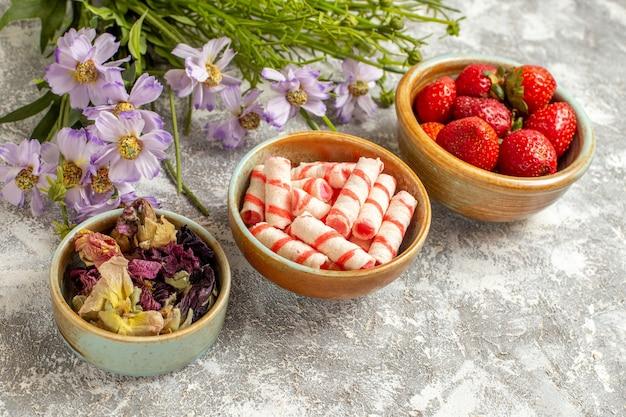 Morangos frescos vermelhos de vista frontal com flores na superfície branca de frutas vermelhas doces