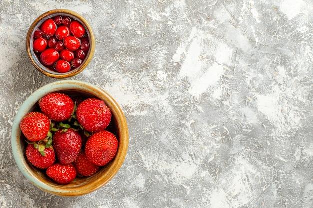 Morangos frescos vermelhos frescos dentro de uma pequena panela na superfície branca com frutas vermelhas baga