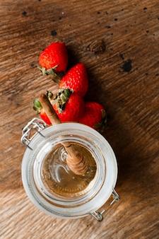 Morangos leigos planas perto de pote de mel