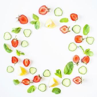 Morangos, limão, pepino e hortelã são forrados sob a forma de uma coroa de flores