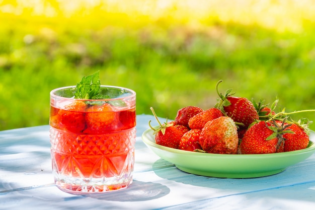 Morangos no prato na mesa e bebida fresca com hortelã