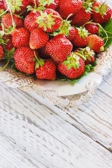 Morangos orgânicos frescos e deliciosos na placa de metal antiga, mesa de madeira. perfeito para uma dieta saudável.