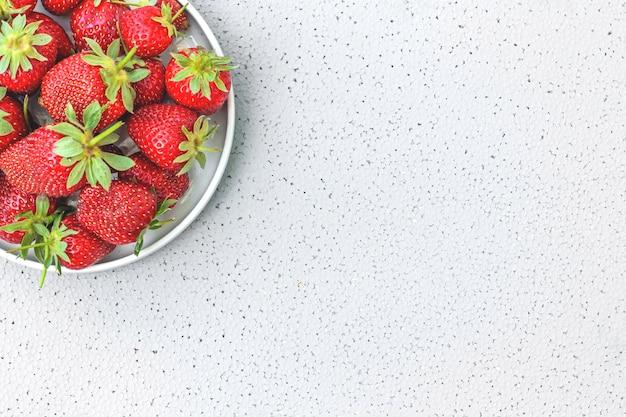 Morangos orgânicos maduros frescos em uma tigela branca. frutas vermelhas suculentas deliciosas em cinza