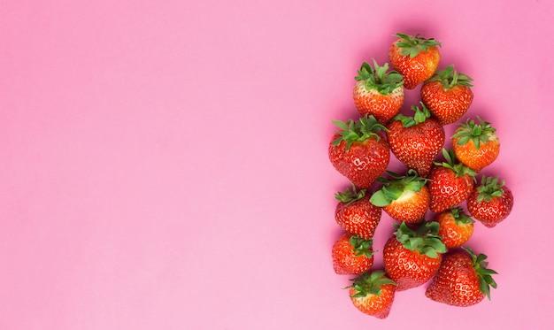 Morangos suculentos maduros em um fundo rosa. conceito criativo de comida mínima.