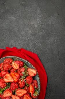 Morangos vermelhos de vista superior dentro do prato em fundo escuro