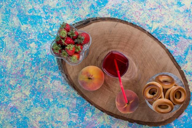 Morangos vermelhos e pêssegos com um copo de suco e biscoitos, vista de cima