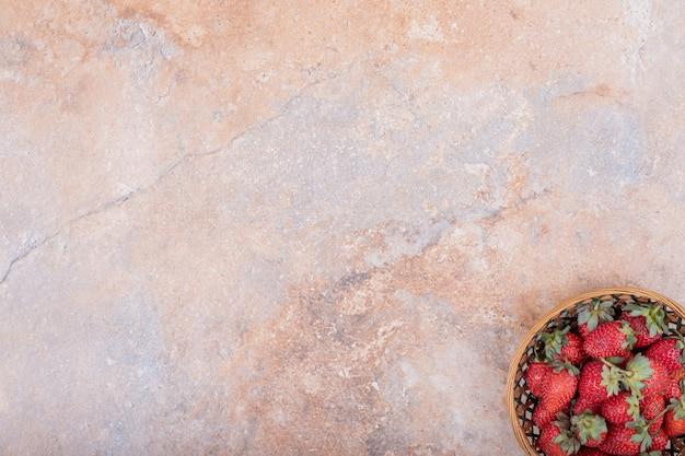 Morangos vermelhos em uma tigela de cerâmica no mármore
