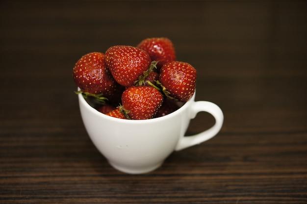 Morangos vermelhos em uma xícara branca