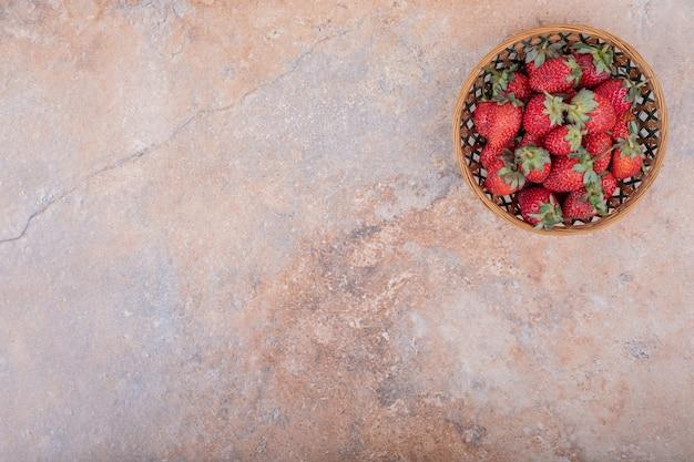 Morangos vermelhos em uma xícara de cerâmica em mármore.