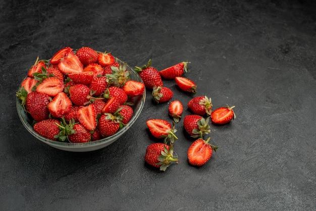 Morangos vermelhos fatiados e frutas inteiras em fundo cinza cor de verão suco de árvore selvagem
