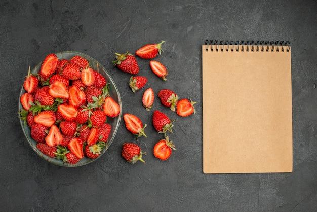 Morangos vermelhos fatiados e frutas inteiras em fundo cinza.