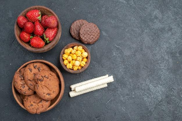 Morangos vermelhos frescos com biscoitos doces em um bolo de biscoito de açúcar de mesa escura de vista superior