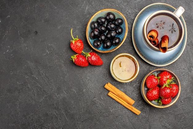 Morangos vermelhos frescos com chá e azeitonas na superfície escura de frutas frescas de baga