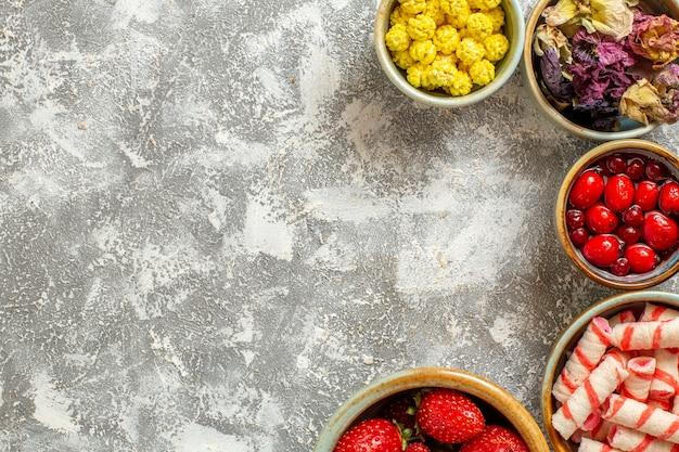 Morangos vermelhos frescos com doces na cor branca de frutas doces de mesa, vista de cima