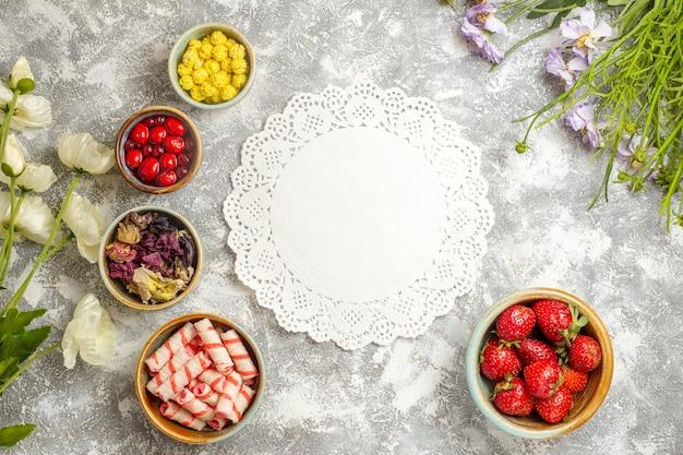 Morangos vermelhos frescos com doces no chão branco