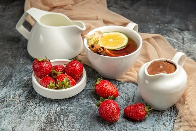 Morangos vermelhos frescos com uma xícara de chá em frutas vermelhas superficiais de luz escura