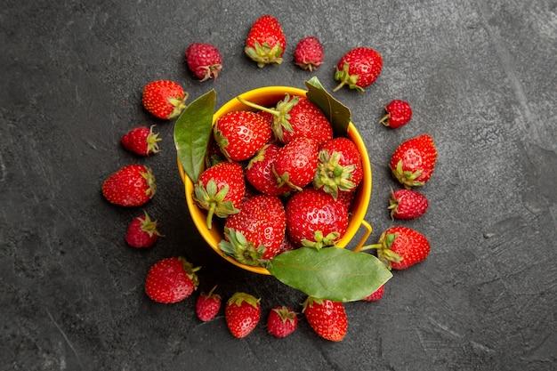 Morangos vermelhos frescos, de cima, alinhados com frutos silvestres de cor escura.