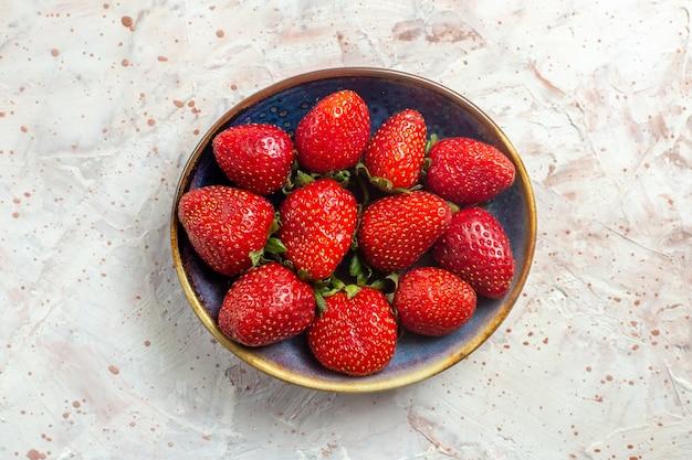 Morangos vermelhos frescos de vista de cima dentro do prato na mesa branca com frutas vermelhas frescas