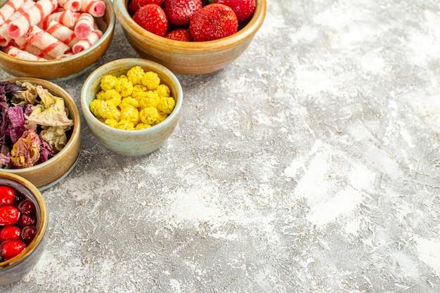 Morangos vermelhos frescos de vista frontal com doces na superfície branca de frutas doces cor de doce