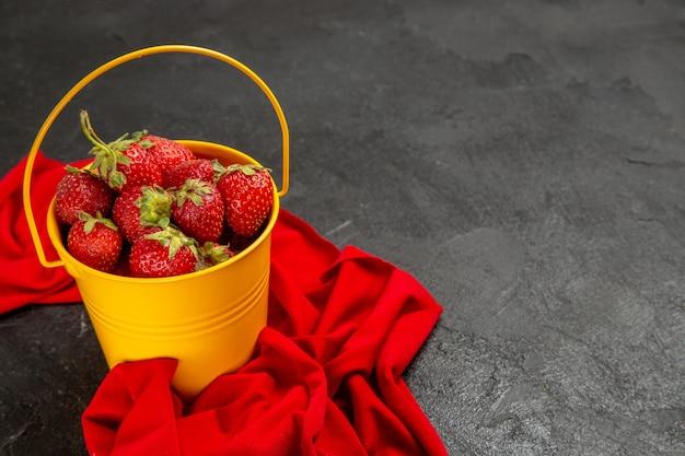 Morangos vermelhos frescos de vista frontal dentro de uma pequena cesta no fundo escuro