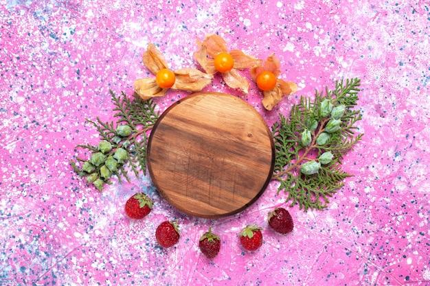 Morangos vermelhos frescos de vista superior com physalises na mesa rosa.