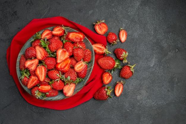 Morangos vermelhos frescos de vista superior dentro do prato em fundo escuro