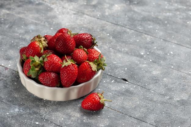 Morangos vermelhos frescos dentro de um prato branco junto com folhas verdes secas em uma mesa cinza, saúde de frutas frescas