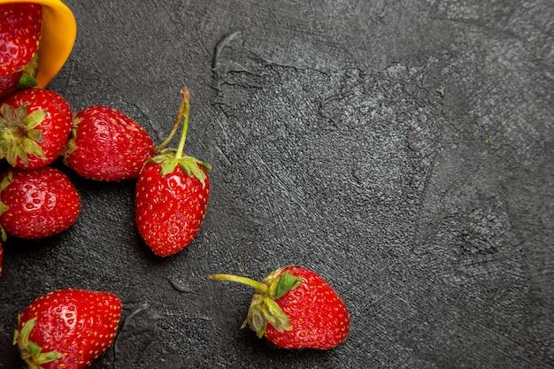 Morangos vermelhos frescos em piso escuro com frutas vermelhas maduras