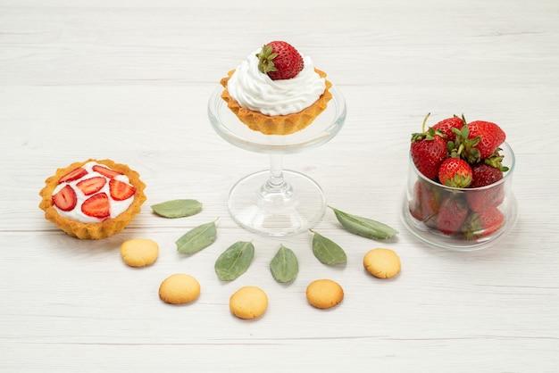 Morangos vermelhos frescos maduros e deliciosas bagas com bolos e biscoitos na mesa de luz. frescura de frutas vermelhas