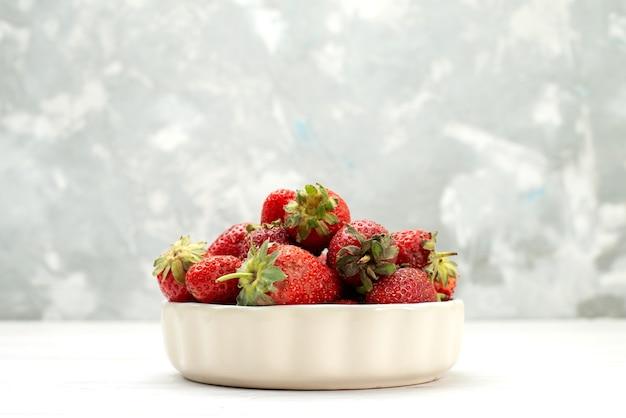 Morangos vermelhos frescos maduros e deliciosas bagas dentro de um prato branco na luz, cor de frutas vermelhas
