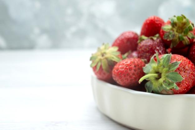 Morangos vermelhos frescos maduros e deliciosos frutos silvestres dentro de um prato branco na luz, cor da foto de frutas vermelhas