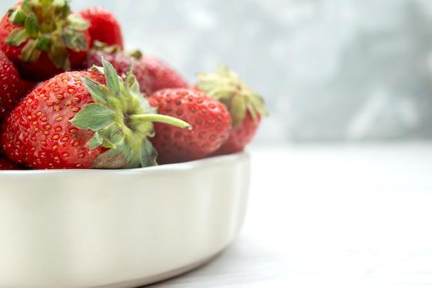 Morangos vermelhos frescos maduros e deliciosos frutos silvestres dentro de um prato branco na mesa de luz