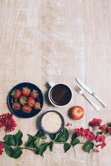 Morangos; xícara de café; aveia; maçã inteira e talheres com flores de buganvílias em pano de fundo de madeira