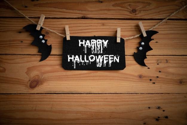 Morcego, aranha e teia de aranha no fundo da mesa de madeira com texto de feliz dia das bruxas.