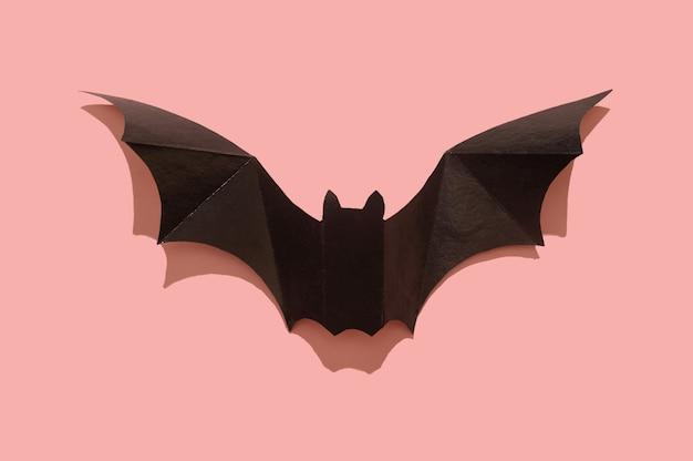 Morcego de papel preto em um fundo rosa. fechar-se. conceito de halloween.