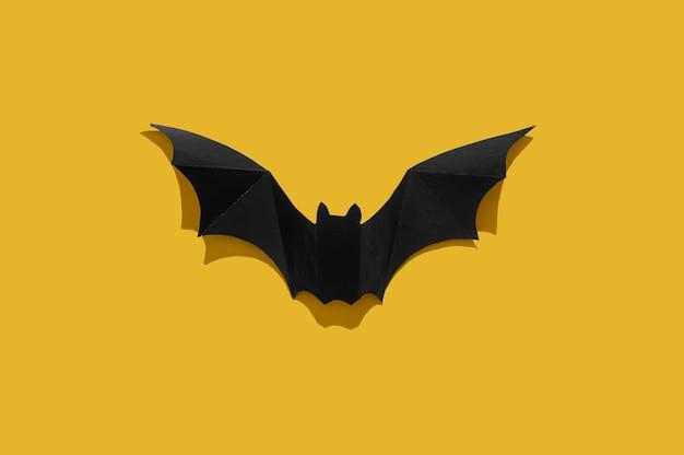 Morcego de papel preto sobre um fundo amarelo. fechar-se.