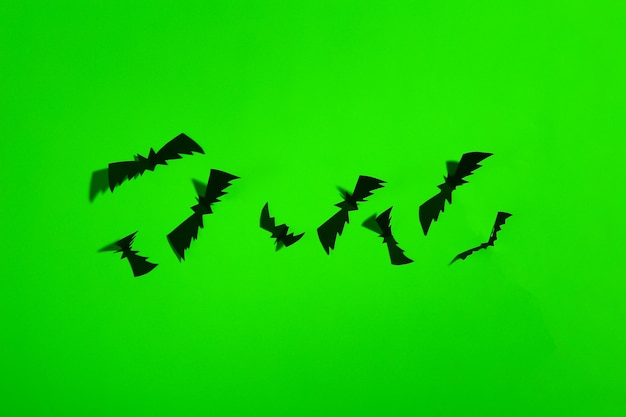 Morcegos cortados em papel em luz neon verde. tema de halloween