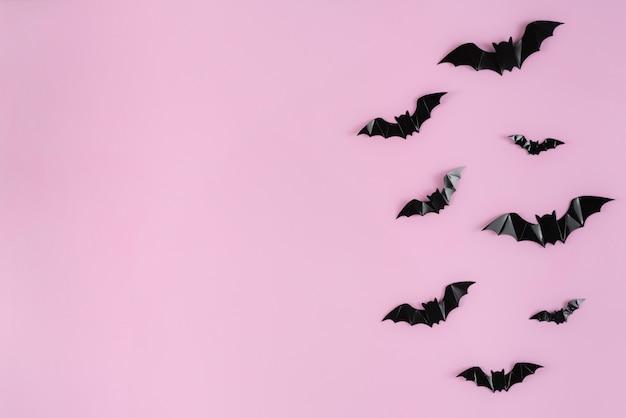 Morcegos de papel preto voando sobre rosa